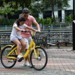 photography-of-girl-riding-bike-beside-man-1005803